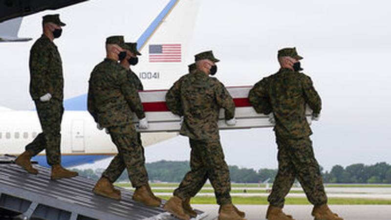 President Joe Biden watches as a carry team moves a transfer case containing the remains of...